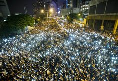 Protesters and student demonstrators hold up their cellphones in a display of solidarity outside the headquarters of the Legislative Council in Hong Kong on Sept. 29. Hong Kong was plunged into the worst political crisis since its 1997 handover as pro-democracy activists took over the streets following China's refusal to grant citizens full universal suffrage.