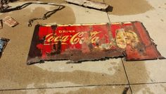 Cleaning up old signs found at abandoned farmstead.  Coca Cola sign is rough,  but still has color after being outside since late 1930's