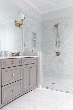 Golden fixtures and a glass wall elevate this white bathroom from ordinary to special and spa-like.