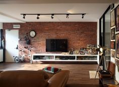 ameublement salon élégant - mur de brique, meuble tv blanc, canapé en cuir marron