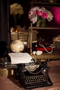 Arrange teal typewriter like this w paper and typed message and by a globe?