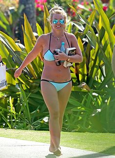 Soaking up the vitamin D while vacationing on the shores of Hawaii, Britney Spears was snapped working the heck out of a pair of barely there blue bikinis on Thursday, March 26—and reading a recent issue of Us Weekly!