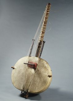 Chordophones, stringed instruments with vertically notched or pierced bridges are found only along the African coast from Senegal to Angola. The unique bridge seen here on this kora lifts the strings on a plane perpendicular to the body instead of parallel to it. Constructed of a calabash resonator covered with sheep or goat hide and bearing nylon strings secured around a wooden neck, the West African kora combines features of the harp and the lute.