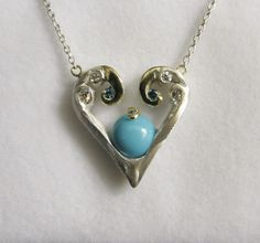 This beautiful pendant features a turquoise center, accented with 18kt yellow gold, white diamonds, and blue diamonds. McNulty Jewelers original design