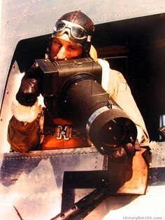 First man to obtain D-Day invasion photographs was cameraman Capt. Dale E. Bikinis, shown with his specially constructed camera.