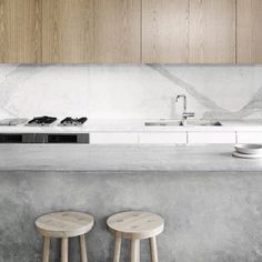 Beautiful kitchen with concrete bench and warmed by timber stools and overhead cupboards