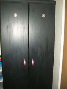 AFTER- wardrobe. Matt black emulsion on sides, satin emulsion on doors, metallic nail vernish!! on the door handles and cameos from cheap picture frames with recycled birthday card pictures.