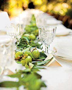 guirnalda a modo de camino de mesa de laureal complementada con higos, caquis, frambuesas y fruta de la pasión