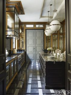 the flooring is granite and quartzite.; Pendants by Circa Lighting hang above the granite-topped kitchen island; the cabinetry is custom made, the range is by De Dietrich, and