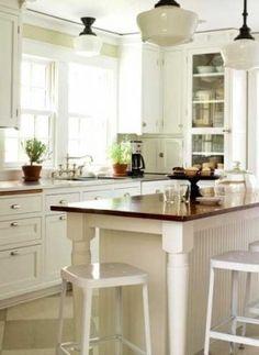 Farmhouse Table Kitchen Island  How do you add vintage style to a kitchen? By adding an island that ties together the new and the old. The island base was built to fit the vintage wood top, which was originally part of a farmhouse table. The beaded board