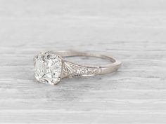 Vintage Art Deco engagement ring set with a 1.55 carat Asscher-cut diamond with GIA certificate stating the diamond is F color/SI1 clarity, with 2 triangle-cut and 4 single-cut diamond side stones. Se