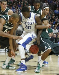 11.12.13 - No. 2 Michigan State 78, No. 1 Kentucky 74 Champions Classic - Michigan State center Adreian Payne (5), Kentucky forward Julius Randle (30) and Michigan State guard Gary Harris, right, struggle for a loose ball during the first half of an NCAA college basketball game in Chicago. (AP Photo/Charles Rex Arbogast)