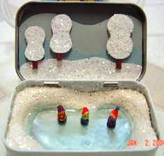 """Skating Tin: I made this during the holidays: it's an altoids tin. I pressed white fimo into the [inside] edges for snow banks, then baked the tin. then I mixed a tiiiny bit of blue food coloring into clear acrylic gloss...I poured the gloss into the """"pond"""" area and let it dry for a few days. Then I cut out paper shapes to fit into the lid, to make the scene, then I painted glue where I wanted glitter."""