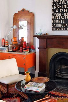 So much character..revamped orange antique dresser, traditional fireplace, modern black art, white tapestry