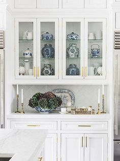 Classic white cabinets with subtle and elegant millwork, sleek and modern brass handles and drawer pulls, filled with a chic traditional mix of antique Chinoiserie vessels, vases and jars, with bronze candlesticks and a blue hydrangea centerpiece arrangement on display. Read more on our Style Guide,