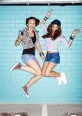 two young women jumping against blue wall. Lifestyle photo