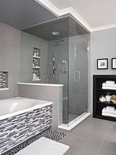 Sheathed in oversize ceramic tile, the shower is grounded with a textured river rock floor. A rain-style showerhead and handheld wand enhance showering. The same linear tile on the vanity backsplash covers the tub surround and niche, adding a third layer Vanity Backsplash, Bathroom Renos, Bathroom Renovations, Gold Bathroom, Bathroom Makeovers, Gray Bathrooms, Bathroom Layout, Small Bathrooms, Basement Bathroom