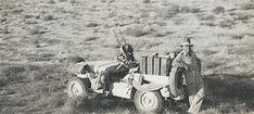 Man standing at the rear of a jeep which is heavily loaded with fuel cans and armed with twin guns at the front