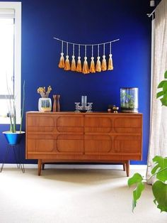 Fascinating Mid-Century Sideboard Design that Steal Your Attention : Fabulous Bedroom Decor With Original Mid Century Sideboard At Corner Bl. Blue Feature Wall, Mid Century Sideboard, Teak Sideboard, Credenza, Style Deco, Tassel Garland, Wooden Flooring, Sweet Home, Bedroom Decor