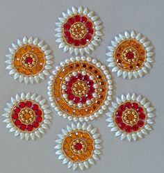 Design inspired from the shape and contours of a bright sun, with red/orange central stones and a pearl periphery
