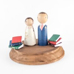 Book themed cake topper with custom peg couple, standard dark brown base, and collection of books. :::: INCLUDED IN THIS LISTING ::::