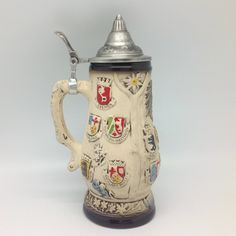 German Edelweiss & Coat of Arms ceramic beer stein with metal lid. This decorative and colorful engraved beer stein makes for a great classic gift or decorative accent to your collection! - Same style