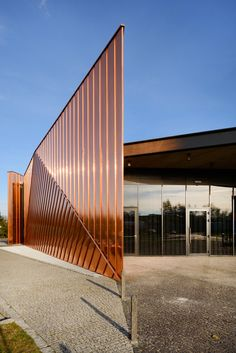 The sculptural shape and copper-clad facades of the exhibition pavilion built in Zory, Poland, to act as a landmark for the town awaken associations with fire.