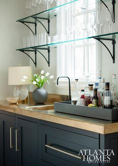 Contemporary bar features black cabinets paired with gold countertops fitted with a gold sink and a sleek black faucet placed under a window lined with stacked glass shelves with slim iron brackets.