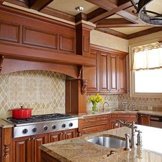 This stone tile backsplash makes an elegant style statement in this traditional kitchen. The darker tones in the tiles echo the warm hues of the wooden cabinets. A trio of decorative tiles directly behind the stovetop lends subtle contrast and texture.