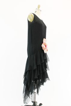 Simply breathtaking! 1920s vintage black silk chiffon gown. This gorgeous beauty is styled in a modern high-low cut. Extreme drop waist that flares into a handkerchief flared hem. Darling large pink flower is sewn onto the front center of this gown. The flower is made out of silk and velvet. Lined in a black silk liner. Liner is cut in a unique reverse sweetheart that comes to a point. This dress is truly amazing. ♥♥♥ Brand: Unknown Size on tag: None Fits like: S Color: Black Material: Silk…