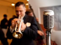 To really set the mood, welcome guests to your wedding with a cocktail hour and live brass band (complete with a retro stand microphone!). Get the best of both worlds by hiring a DJ to take over the party tunes for the reception or after party.