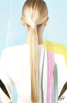 """How to get this sleek ponytail: 1) Start by flat-ironing your hair. 2) Leave two small sections of hair out in the front, pulling everything else back into a low ponytail at the nape of your neck. 3) Take the two remaining sections and pull them back to your elastic, overlapping them to make a """"criss-cross"""" effect, securing them underneath your ponytail with pins."""