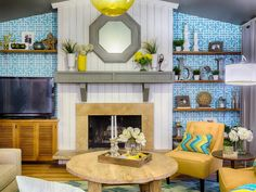 This eclectic leaving room features blue vintage-style wallpaper and open wood shelving. The fireplace boasts a cottage-style white paneled surround with a gray mantel. Pops of yellow add fun, bright color to the space.