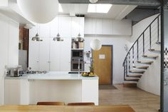 stairway to loft above kitchens | Above: Opaque globe lighting mixes with aluminum pendants; for a ...