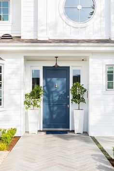 White paneled house featuring a blue front door with a brass knocker flanked by tall white planers bring a lush green accent to the front entry door design.