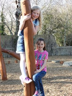 Girls playing on natural timber play equipment at Orchard Meadow in Spelthorne