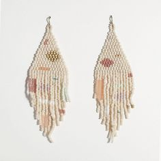 """Celebrating the light and pure joy of summer time, these delicately hand beaded earrings perfectly encapsulate the subtle peachy warmth, golden glow and color palette of the season. Hand sewn and woven with needle, thread, Czech, Japanese glass seed beads and gold filled ear wire. Measures approximately 1.25"""" x 5"""" Salihah Moore is an artist and designer based in Boulder, Colorado. Gathering inspiration from textiles and contemporary design, Salihah strives to make new the ancient c..."""