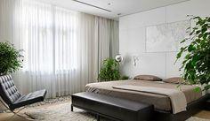 Plantas y flotes naturales ponen el toque green y purifican el aire en este dormitorio moderno y elegante, decorado en tonos tierra.