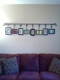 DONE for around $20! Dollar store picture frames, spray paint, scraps of scrapbook paper, Cricut cut letters, curtain rod, ribbon and eye hooks from Walmart.  LOVE IT!