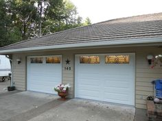 Clopay Classic insulated raised panel steel garage doors with Orleans decorative wrought iron windows. Installed by Hung Right Doors LLC. www.clopaydoor.com