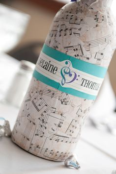Modge Podged sheet music on wine bottles for table decorations and used the music staff to place our symbol and names.