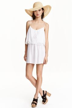 Sleeveless playsuit: Playsuit in a cool weave with a wide top with inset lace trims at the front, an elasticated seam at the waist, narrow adjustable shoulder straps and short legs.