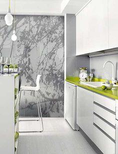 Painel de sombras da natureza complementam a contemporaneidade desta cozinha branca com toques frescos de verde