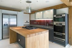Oak central island with gas hob built in, glass hob hood above, stainless steel kitchen appliances and modern style dark grey kitchen cabinets.