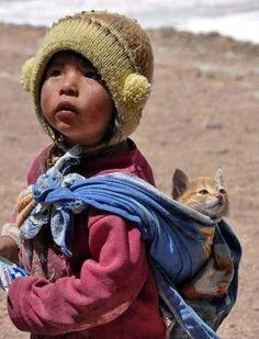 Niña del altiplano andino llevando su gatito como las madres llevan a sus hijos