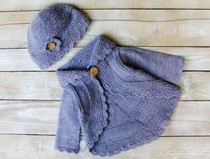 This sweater set will fit baby girls 6 to 12 months old.  Hand knitted from 100% pure wool, this lilac purple cardigan features an over-sized