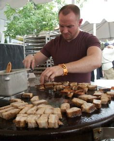 PORTLAND, OREGON - September 20, 2012 - Matt Ives cooks up the maple glazed pork belly for Naomi Pomeroy's maple glazed pork belly sandwich with pickled watermelon slaw on a semolina bun on the Evo Circular Cooktop. The Sandwich Invitational, the first event of Feast Portland food festival, was held in Director Park featuring a variety of sandwiches prepared by notable chefs.