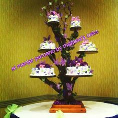 Butterfly quinceañera cake on tree stand.