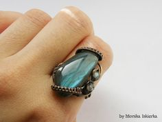 Muirin-wire wrapped ring with big grey labradorite with beautiful blue, turquoise flash. Oxidized/tinted, hammered and polished copper wire for ancient, old looking vintage effect. Adjustable. Gemstone size is about 2,8 x 1,4 cm. 100% handmade. Made by Monika Iskierka.
