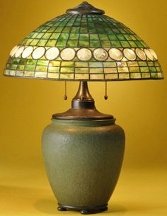 lighting, Massachusetts, Grueby Pottery table lamp with mosaic glass shade, art pottery, glass, and metal base Boston, Massachusetts. Geometric leaded glass patterned domed freen glass shade with a border of white opalescent jewels over a three socket cluster with acorn pulls fitted to bulbous green glazed Grueby base, bass drilled through mark, paper Grueby label, price label $10.00, and no. B 8627 Circa 1901-1910